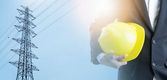 Double exposure Engineer with safety helmet on high voltage pole royalty free stock photo