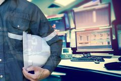 Double exposure of Engineer or Technician man holding safety hat. With computer monitor control room for stock and control process industrial business concept Royalty Free Stock Photo