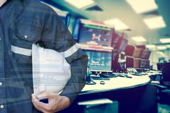 Double exposure of Engineer or Technician man holding safety hat. With computer monitor control room for stock and control process industrial business concept Stock Photo