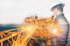 Double exposure of Engineer or Technician man with safety helmet. Operated platform or plant by using tablet with offshore oil and gas platform background for Stock Photography