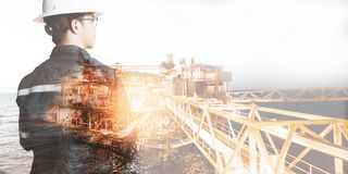 Double exposure of Engineer or Technician man with safety helmet operated platform or plant by using tablet with offshore oil and royalty free stock images