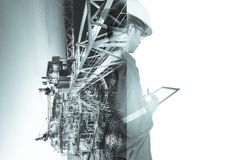 Double exposure of Engineer or Technician man with safety helmet operated platform or plant by using tablet with offshore oil and royalty free stock image
