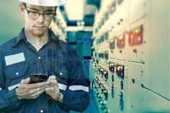 Double exposure of Engineer or Technician man using smart phone. For control electric in switch gear electrical room of oil and gas platform or plant industrial royalty free stock images