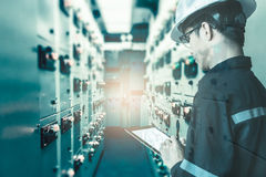 Double exposure of Engineer or Technician man working with tab. Let in switch gear electrical room of oil and gas platform or plant industrial for monitor royalty free stock photo