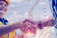 Double exposure engineering and construction concept. Industrial engineer wear safety helmet shaking hands stock image