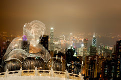 Double exposure Giant Buddha sitting on lotus in Hong Kong,Night view of the peak city life. royalty free stock photos