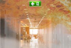 Double exposure green emergency exit sign in hospital showing th. E way to escape with fire stock photos