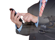 Double exposure of hand hold and touch screen smartphone. Double exposure of businessman hand touch screen smartphone with airport blurry background Royalty Free Stock Photo