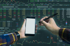 Double exposure of Hand holding blank smart phone checking finan. Cial stats on screen for trading stock concept Stock Images