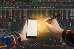 Double exposure of Hand holding blank smart phone checking finan. Cial stats on screen for trading stock concept Royalty Free Stock Image