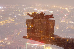 Double exposure of hand holding gift over night cityscape Royalty Free Stock Photos
