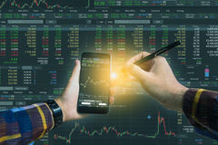 Double exposure of Hand holding smart phone checking financial s. Tats on screen for trading stock concept Royalty Free Stock Photo