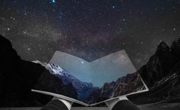 Double exposure, hand opening book and night landscape of mountain and stars on the sky royalty free stock photo