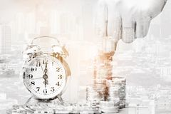 Double exposure of Hand putting money coins to stack of coins and retro alarm clock on city background for Real estate investments royalty free stock photo