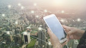 Double exposure of hand touch screen on Smartphone and city. Concept in connection Stock Photos