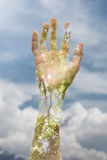 Double exposure of a hand and a tree promoting environmental sus. A light-skinned person`s hand raised up against a backdrop of clouds Royalty Free Stock Images
