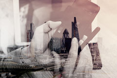 Double exposure of Hand using mobile payments online shopping,omni channel,icon customer network,in modern office wooden. Desk,London city buildings,eyeglass stock photo