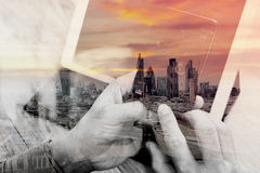 Double exposure of Hand using smart phone payments online shopping,omni channel,icon customer network,in modern office wooden. Desk,London city buildings stock photos