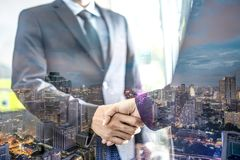 Double exposure of handshake and city, Business handshake and business people royalty free stock image