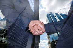 Double exposure of handshake and city.handshake and business people concepts. Two men shaking hands isolated on cityscape background. Close-up image of Royalty Free Stock Images