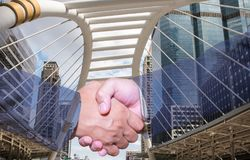 Double exposure of handshake and city.handshake and business people concepts. Two men shaking hands  on cityscape background. Close-up image of handshake Royalty Free Stock Photo