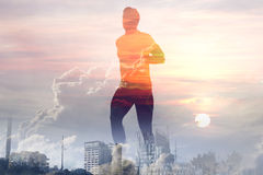 Double exposure of healthy young man running after work. royalty free stock photography