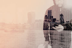 Double exposure of hipster male in a hood hand using mobile phon. E,front view,London architecture buildings Royalty Free Stock Photo