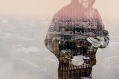 Double exposure of hipster male in a hood hand using mobile phon. E,front view,London architecture buildings Stock Images