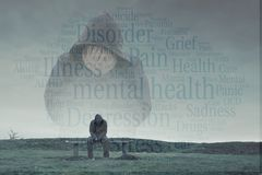 A double exposure of a hooded figure with his head in his hands over a lonely hooded figure sitting on a park bench, looking sad, royalty free stock image