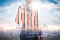 The double exposure image of the businessman point to business chart overlay with cityscape image. The concept of modern life, bus royalty free stock photo