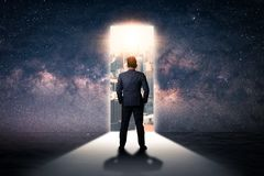 The double exposure image of the businessman standing front of the door is opening during sunrise overlay with cityscape and astro. Image. The concept of modern royalty free stock photography
