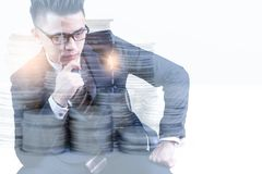 The double exposure image of businessman thinking overlay with coin stack and white copy space. The concept of accounting, business, financial, economy and stock photo
