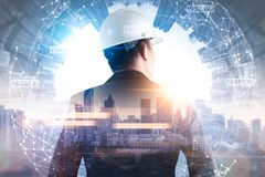 The double exposure image of the engineer standing back during sunrise overlay with cityscape image and futuristic hologram. stock photo