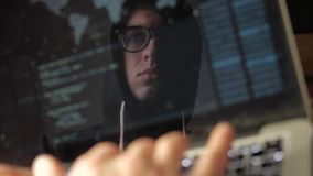 Double exposure: man hacker in glasses working at a laptop. Hacker writes blue code, reflection in the monitor. Hacker writes blue code, reflection in the stock video footage