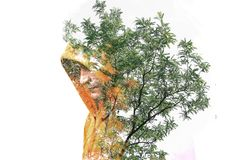Double exposure of a man in a hood. Double exposure of a guy among the leaves. Creative art illustration of a male in a hood. stock photography