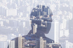 Double exposure of man over cityscape, rear view Stock Photo