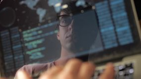 Double exposure: man programmer in glasses working at a laptop. Programmer writes blue code, reflection in the monitor. Programmer writes blue code, reflection stock video