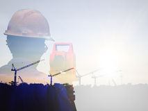 Double exposure man survey and civil engineer stand on ground working in a land building site over Blurred construction worker on Royalty Free Stock Image