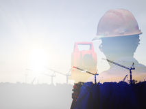 Double exposure man survey and civil engineer stand on ground working in a land building site over Blurred construction worker on Stock Photography