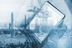 Double exposure, a man using digital tablet and buildings construction with cityscape royalty free stock photo