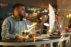 Double exposure of man working in office and illuminated city at night stock image