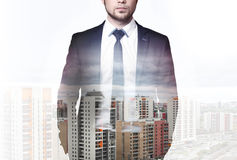 Double exposure of modern city and businessman wearing an elegant suit, standing with his hands in pockets Stock Photography