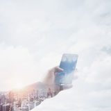 Double exposure photo businessman holding modern smartphone hand, touching empty screen. Reflection of clouds and Stock Image