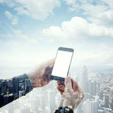 Double exposure photo businessman holding modern smartphone hands. Panoramic view contemporary city and clouds Royalty Free Stock Image