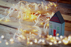 Double exposure photo of decorative house next to gold garland lights on wooden background. copy space. retro filtered Stock Images
