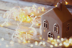 Double exposure photo of decorative house next to gold garland lights on wooden background. copy space. retro filtered Stock Photo