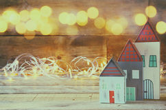 Double exposure photo of decorative house next to gold garland lights on wooden background. copy space. retro filtered Stock Photography