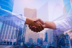 Double exposure photo. Photo mix building city and Shake hands. They are join hands mean teamwork and spirit beside building background. Photo concept for stock photo