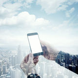 Double exposure photo modern smartphone holding male hands. Panoramic view contemporary city and clouds background Royalty Free Stock Images