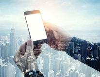 Double exposure photo modern smartphone holding male hands. Panoramic view contemporary city and clouds background Stock Images